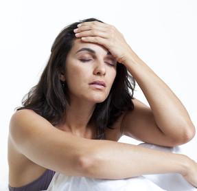 Schöne Frau mit Kopfschmerzen im Bett sitzend